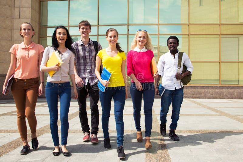 Groep diverse studenten die samen lopen stock afbeelding