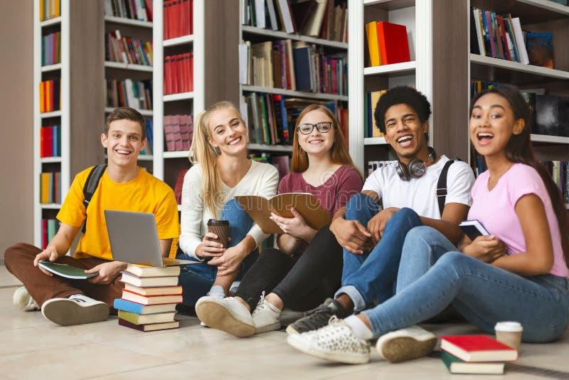 Groep diverse tienerklasgenoten die op bibliotheekvloer zitten royalty-vrije stock afbeelding