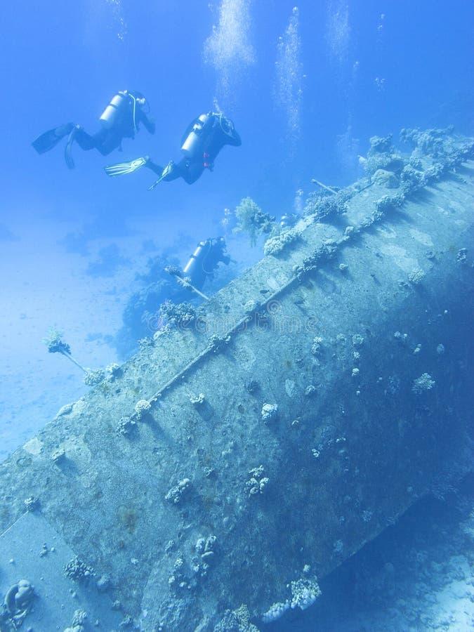 Groep duikers boven het wrak van oud schip bij de bodem van tropische overzees, onderwaterlandcape royalty-vrije stock afbeeldingen