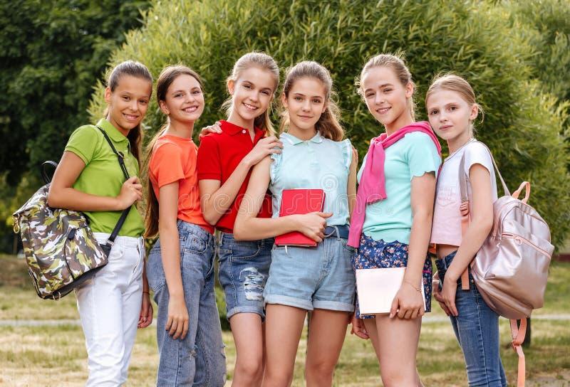 Groep en schoolkinderen die lachen omhelzen stock afbeelding