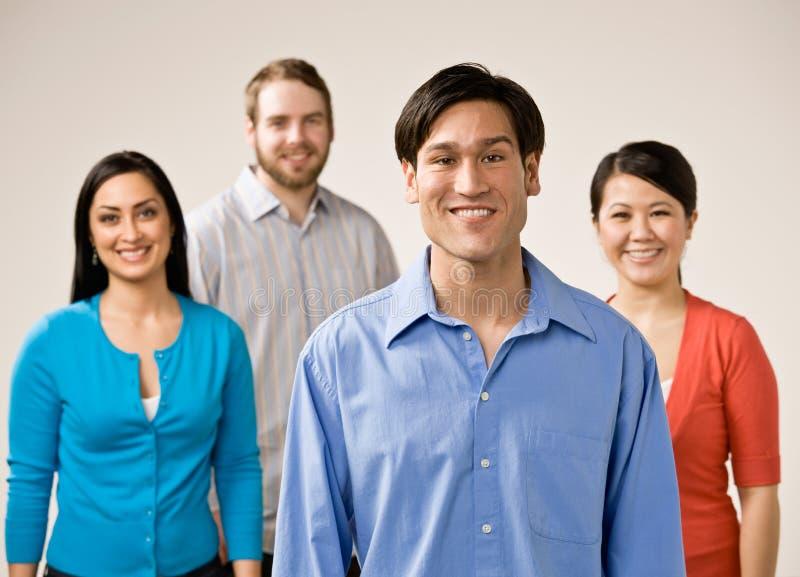Groep en vrienden die glimlachen stellen royalty-vrije stock afbeeldingen