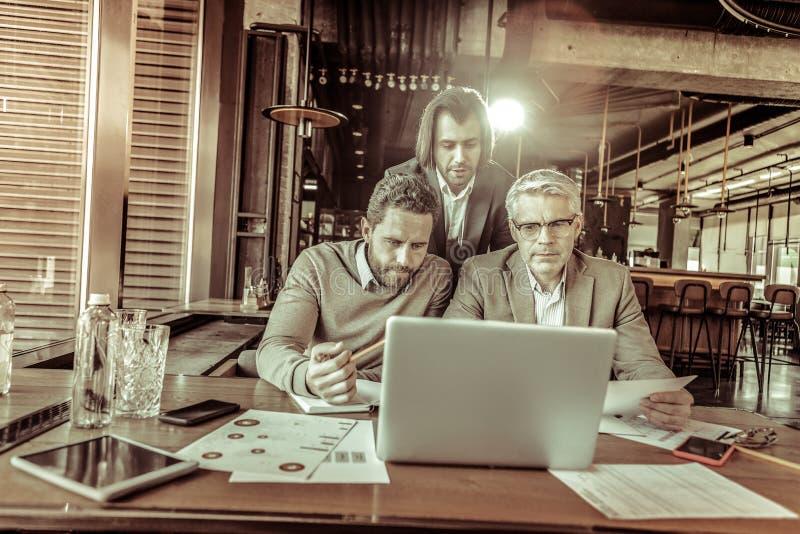 Groep ernstige partners die bij hun project samenwerken royalty-vrije stock foto