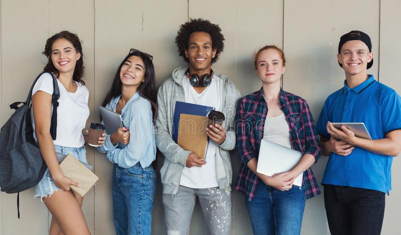 Groep etnische tienerstudenten met omslagen en schooltassen stock afbeeldingen