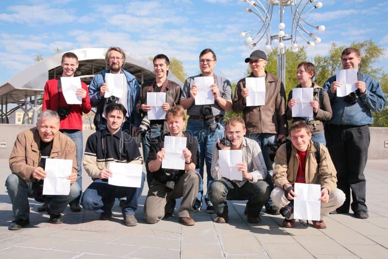 Groep fotografen met bladen van document stock fotografie