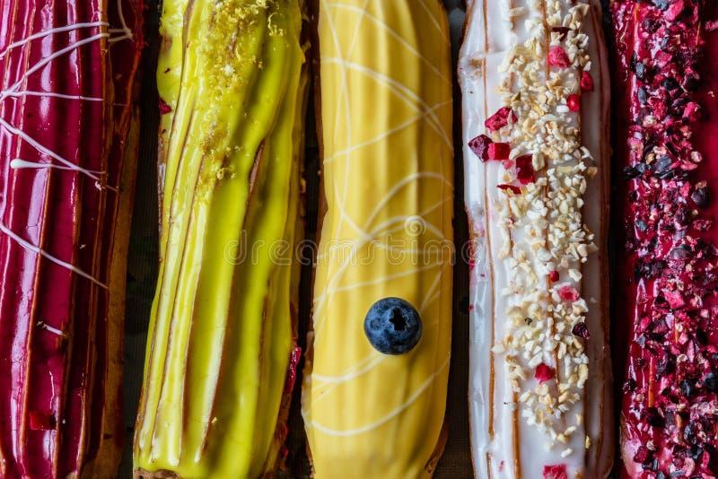 Groep Franse desserteclair cake met witte gele en rode room en glanzende decoratie stock foto