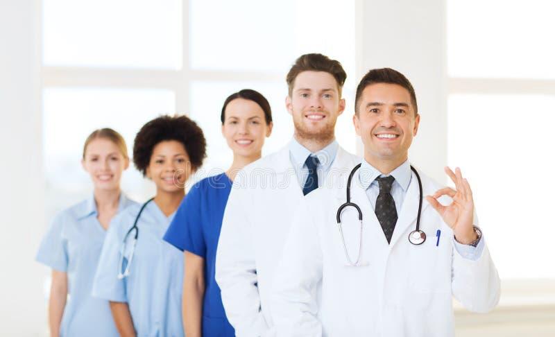 Groep gelukkige artsen bij het ziekenhuis royalty-vrije stock afbeelding