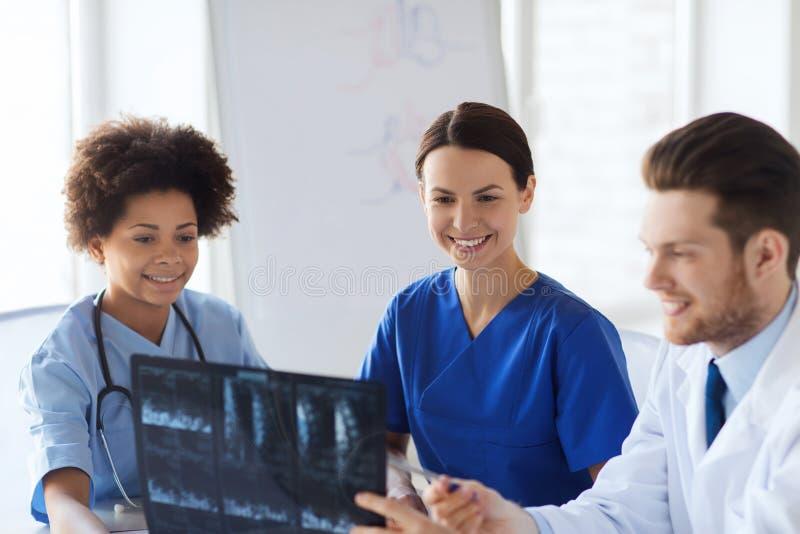 Groep gelukkige artsen die x-ray beeld bespreken stock afbeeldingen