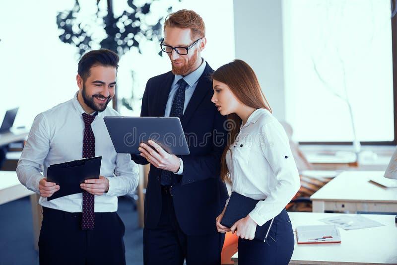Groep gelukkige bedrijfsmensen die op kantoor tijdens commerciële vergadering bespreken stock foto's