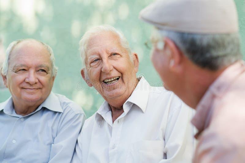 Groep gelukkige en bejaarden die lachen spreken stock foto's