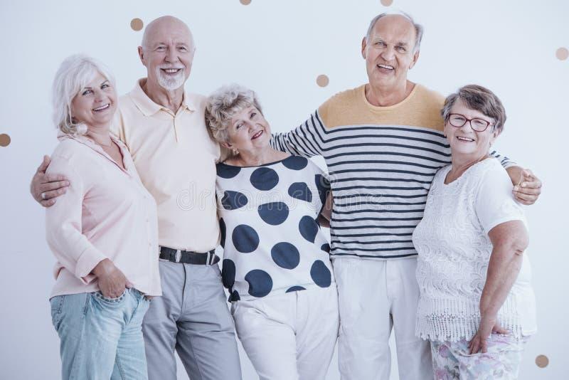Groep gelukkige en glimlachende bejaarde mensen die van een vergadering genieten royalty-vrije stock afbeelding