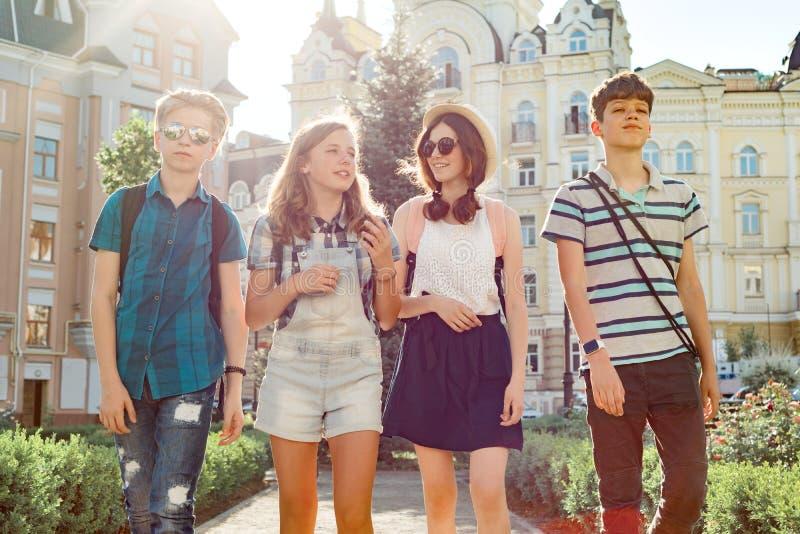 Groep gelukkige glimlachende sprekende vriendentieners, jongeren die in de stad op zonnige de zomeravond lopen Vriendschap en men stock foto