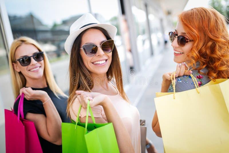 Groep gelukkige glimlachende vrienden die in de stad winkelen stock foto