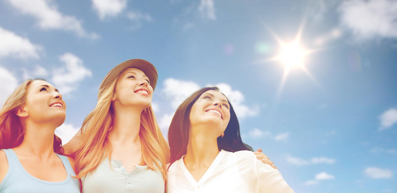 Groep gelukkige glimlachende vrouwen of vrienden over hemel stock afbeeldingen