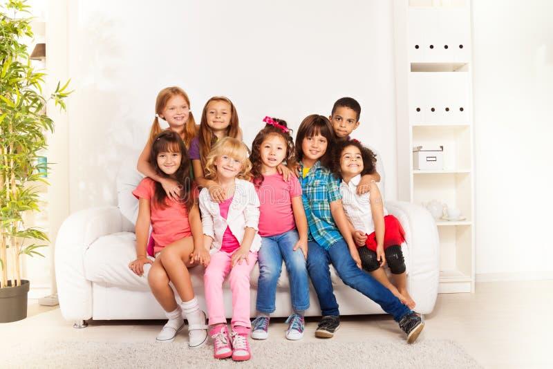 Groep gelukkige het koesteren jonge geitjes thuis stock foto's