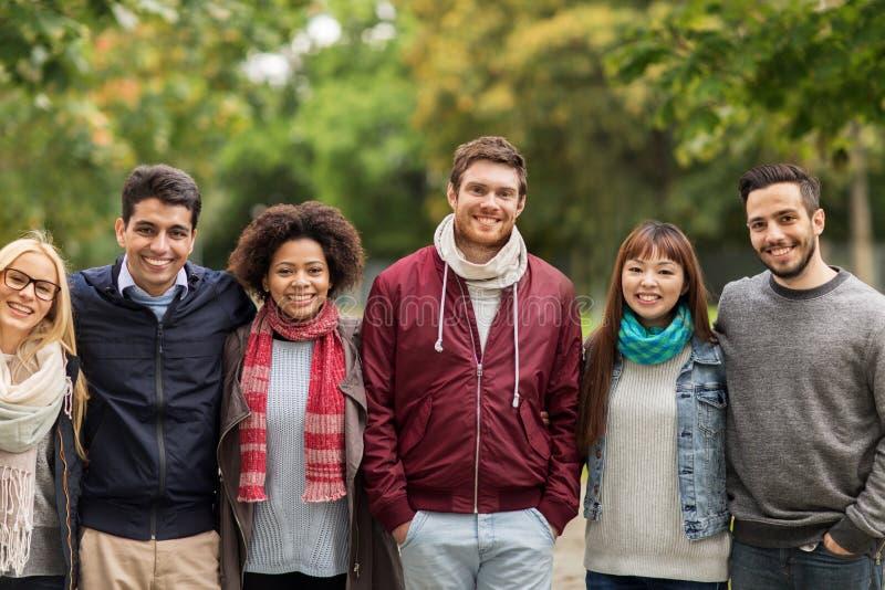 Groep gelukkige internationale vrienden bij park royalty-vrije stock foto