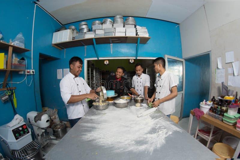 Groep gelukkige jonge Aziatische gebakjechef-kok die deeg met bloem, profesionalchef-kok voorbereiden die bij keuken werken royalty-vrije stock afbeeldingen