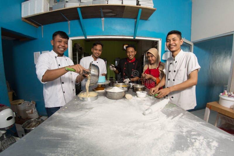 Groep gelukkige jonge Aziatische gebakjechef-kok die deeg met bloem, profesionalchef-kok voorbereiden die bij keuken werken stock afbeeldingen