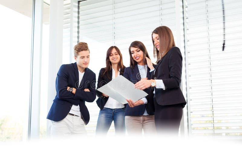 Groep gelukkige jonge bedrijfsmensen in een vergadering op kantoor royalty-vrije stock afbeelding