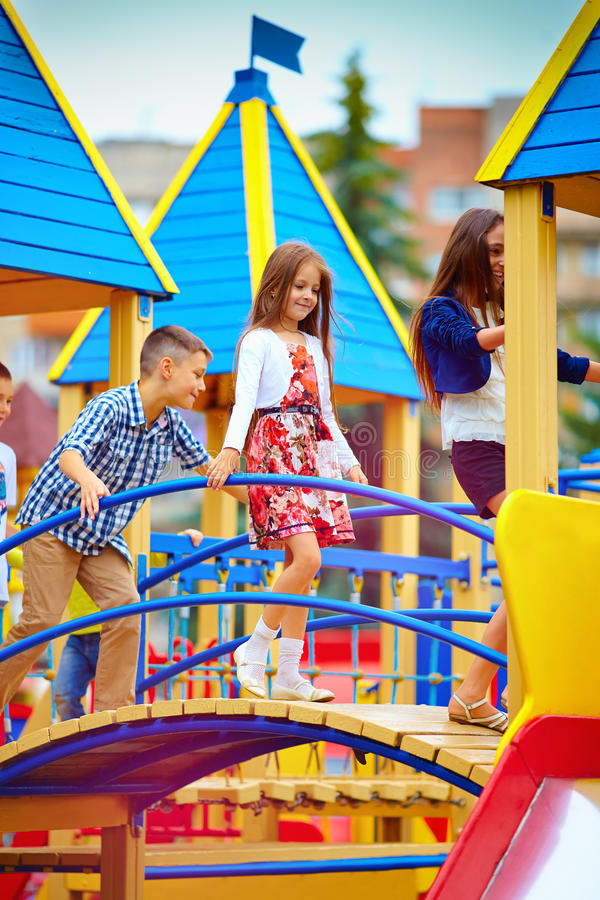 Groep gelukkige jonge geitjes die pret op stuk speelgoed kasteel, op speelplaats hebben royalty-vrije stock fotografie