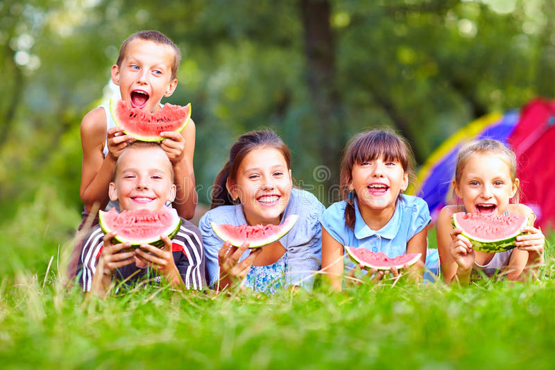 Groep gelukkige jonge geitjes die watermeloenen eten royalty-vrije stock foto