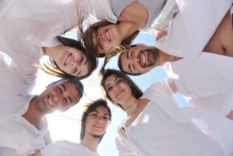 Groep gelukkige jonge mensen in cirkel bij strand royalty-vrije stock fotografie