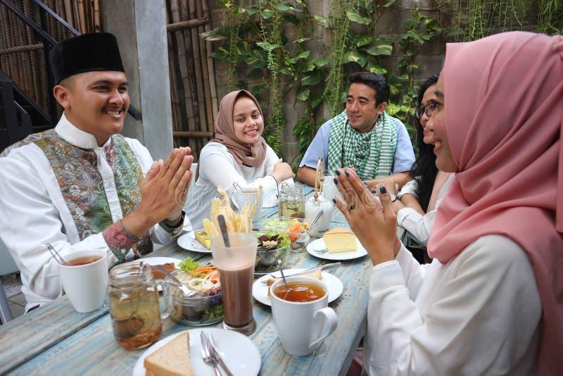 Groep gelukkige jonge moslim die elke anderen in eettafel omhelzen stock foto's
