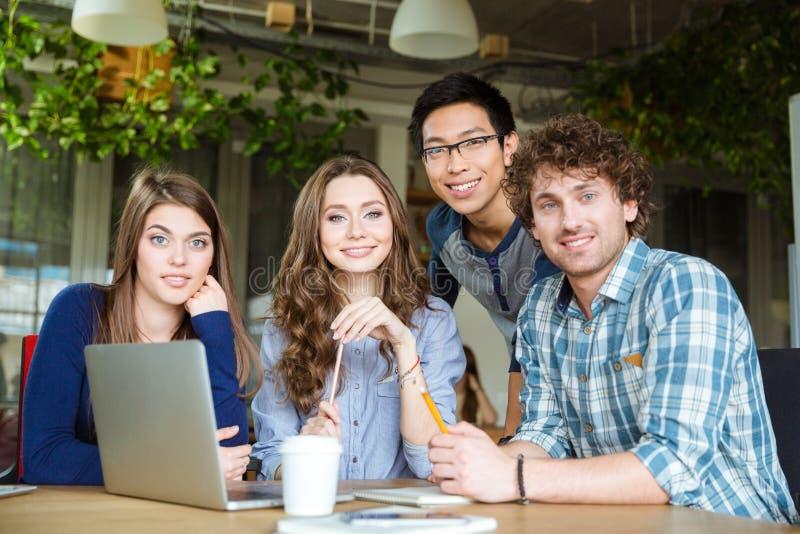 Groep gelukkige jonge studenten die bij de lijst zitten stock foto