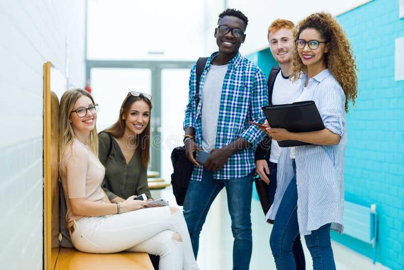 Groep gelukkige jonge studenten die camera op een universiteit bekijken stock afbeelding