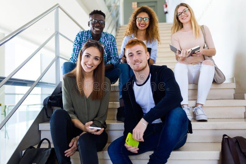 Groep gelukkige jonge studenten die camera op een universiteit bekijken stock fotografie