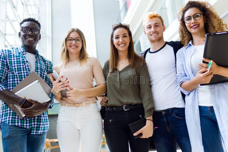 Groep gelukkige jonge studenten die camera op een universiteit bekijken royalty-vrije stock foto's