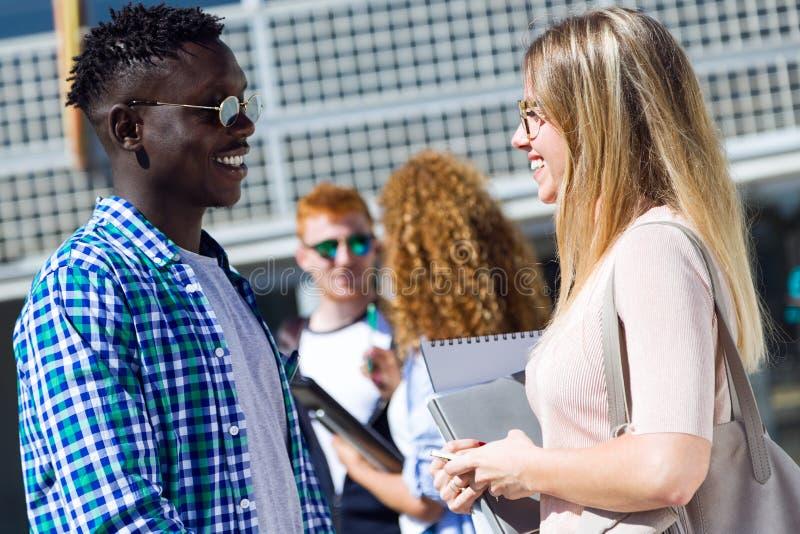 Groep gelukkige jonge studenten die op een universiteit spreken royalty-vrije stock afbeelding