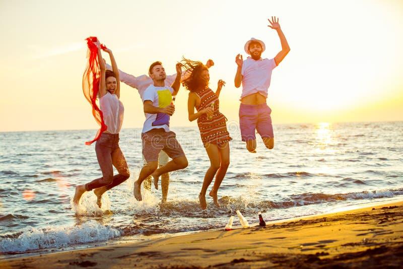 Groep gelukkige jongeren die bij het strand op mooie de zomerzonsondergang dansen royalty-vrije stock foto
