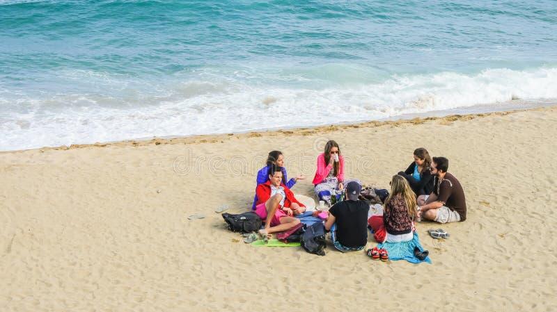 Groep gelukkige jongeren die in een cirkel op het zandige strand zitten stock foto