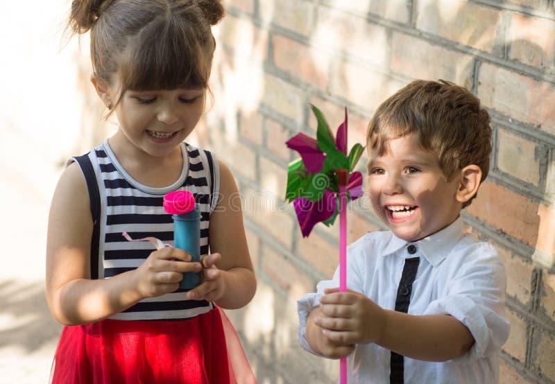 Groep gelukkige kinderen die in openlucht spelen Jonge geitjes die pret in de zomerpark hebben royalty-vrije stock afbeelding