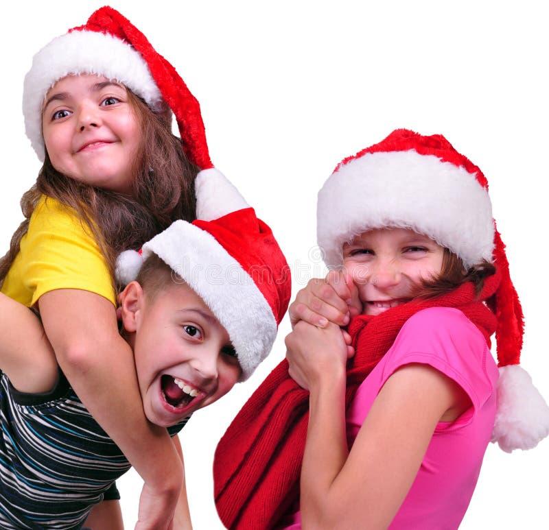Groep gelukkige kinderen met de rode hoeden van Santa Claus stock foto