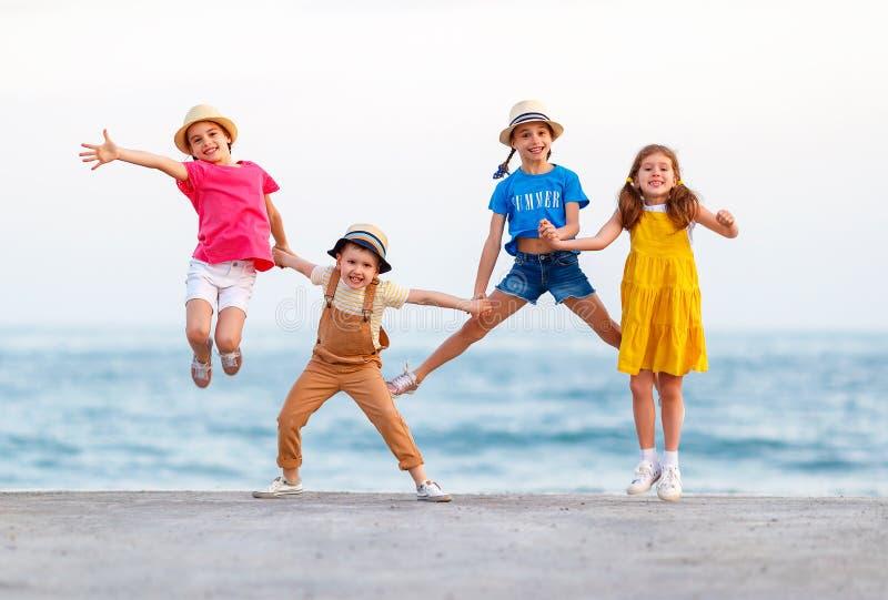 Groep gelukkige kinderensprong door overzees in de zomer stock fotografie