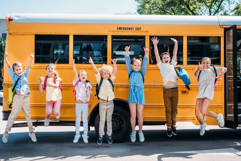 groep gelukkige leerlingen die voor school bus en het kijken springen stock foto