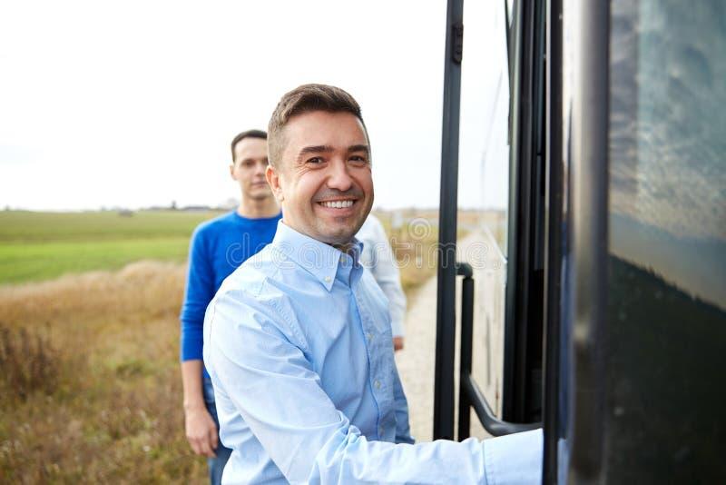 Groep gelukkige mannelijke passagiers die reisbus inschepen stock afbeeldingen