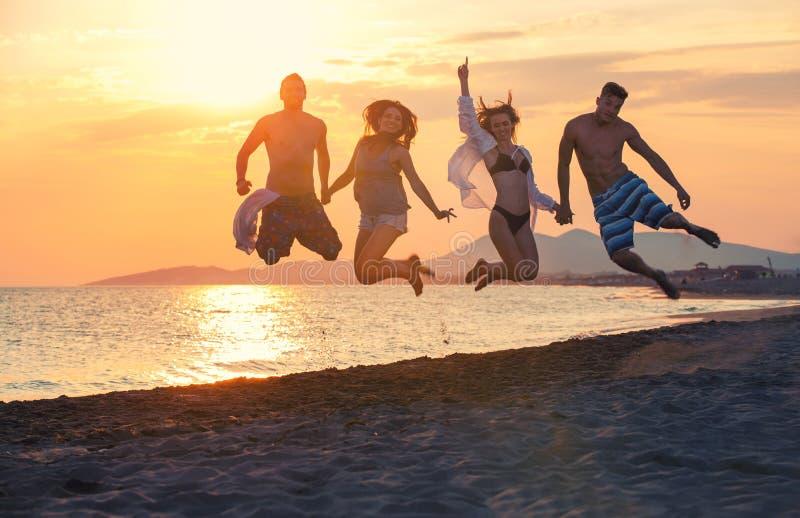 Groep gelukkige mensen die en binnen overzees op zonsondergang dansen springen royalty-vrije stock afbeelding
