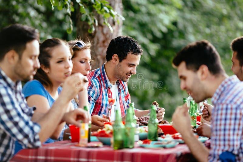 Groep gelukkige mensen die voedsel in openlucht eten royalty-vrije stock afbeelding