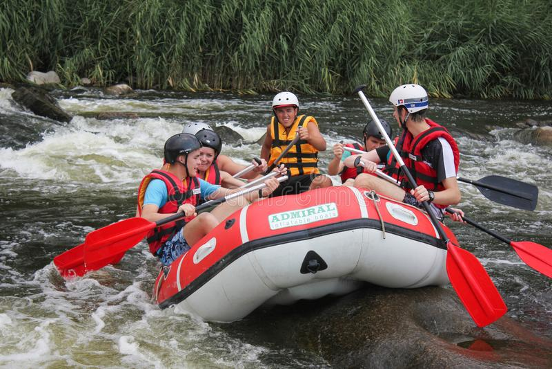 Groep gelukkige mensen met gids die whitewater en op rivier, uiterste en pretsport rafting roeien royalty-vrije stock afbeeldingen