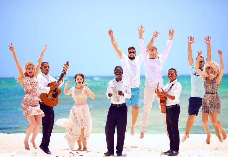 Groep gelukkige mensen op viering het exotische huwelijk met musici, op tropisch strand royalty-vrije stock afbeeldingen