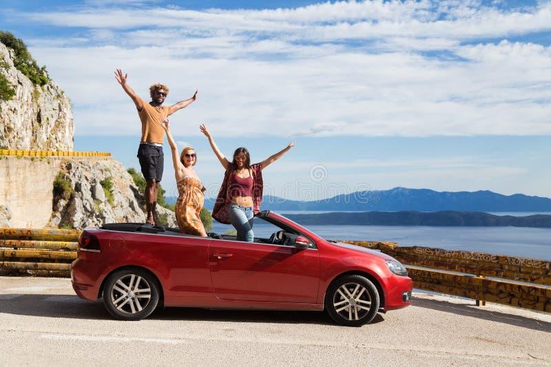 Groep gelukkige mensen in rode convertibele auto stock afbeelding