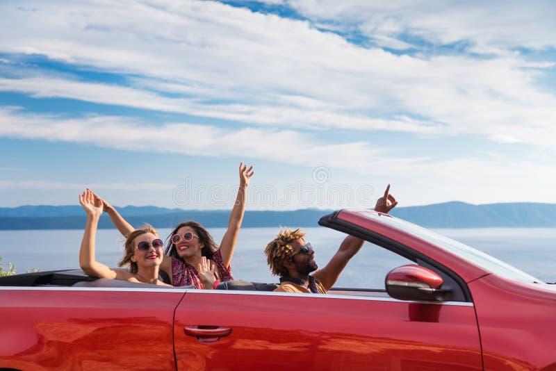 Groep gelukkige mensen in rode convertibele auto stock fotografie
