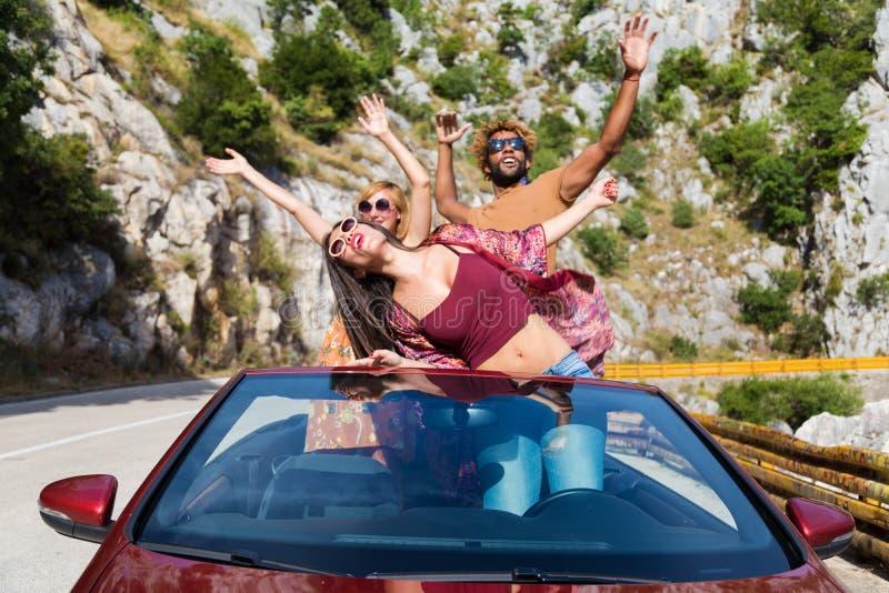 Groep gelukkige mensen in rode convertibele auto stock afbeeldingen