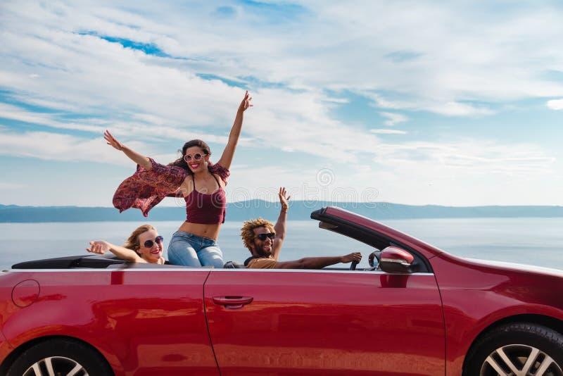 Groep gelukkige mensen in rode convertibele auto stock foto