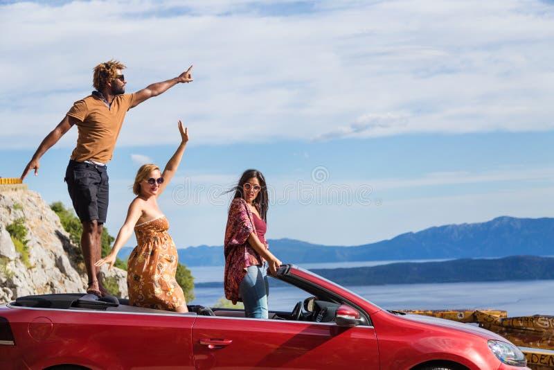 Groep gelukkige mensen in rode convertibele auto stock foto's