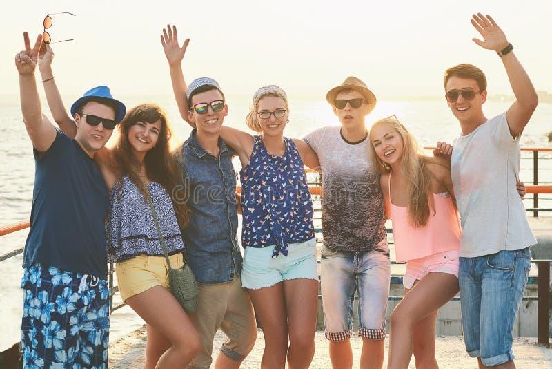 Groep gelukkige onbezorgde vrienden die uit bij de zonnige de zomerkust hangen royalty-vrije stock fotografie