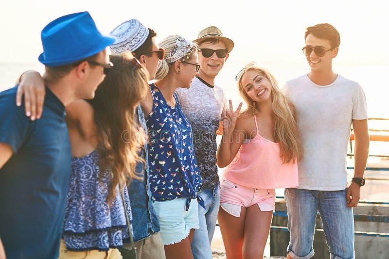 Groep gelukkige onbezorgde vrienden die uit bij de zonnige de zomerkust hangen stock afbeelding