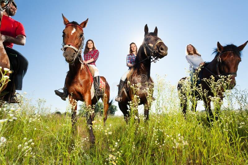 Groep gelukkige paardruiters in bloemrijke weide stock afbeeldingen